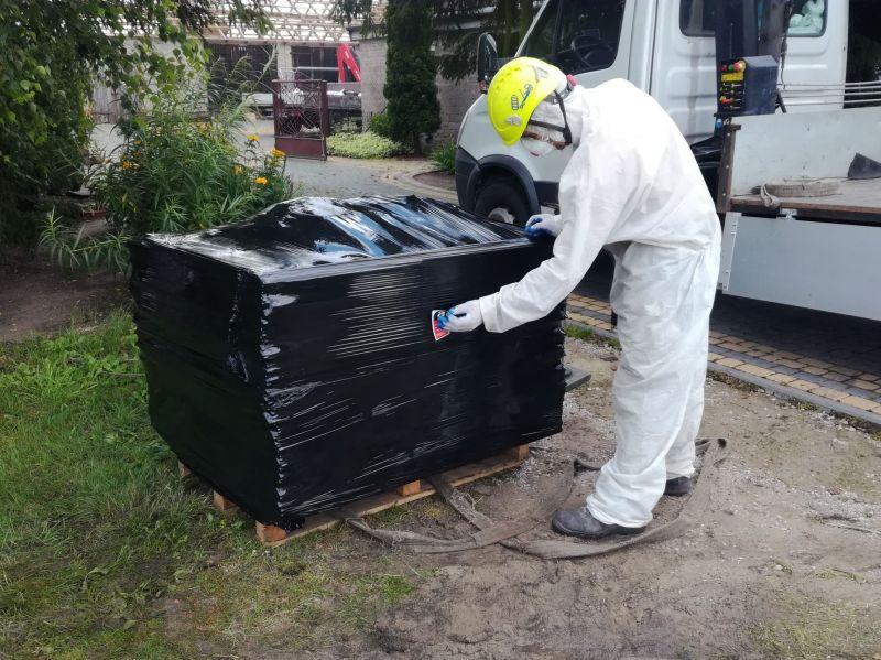 Azbest to materiał bardzo niebezpieczny. Włókna azbestowe które uwalniają się do powietrza podczas wykonywania prac, takich jak demontaż płyt azbestowych, mogą zalegać w płucach i powodować choroby, takie jak pylica azbestowa czy nawet nowotwór płuc. Dzięki rosnącej świadomości społeczeństwa, coraz więcej osób decyduje się na usunięcie azbestu ze swojego otoczenia, korzystając z usług profesjonalistów. Materiały budowlane zawierające azbest zastępowane są innymi, nieszkodliwymi materiałami. Przed przystąpieniem do transportu odpadów azbestowych, wszystkie materiały zawierające azbest są zabezpieczane, zgodnie z obowiązującymi przepisami. Na przedstawionym zdjęciu nasz pracownik zabezpiecza zdemontowane materiały zawierające azbest tj. płyty azbestowo-cementowe faliste. Płyty eternitowe układamy na paletach, zabezpieczamy folią i oznaczamy etykietą ?Uwaga, zawiera azbest?. Tak przygotowane odpady azbestowe są gotowe do przekazania na specjalistyczne składowisko odpadów zawierających azbest celem ich unieszkodliwienia. Zdjęcie przedstawia pakowanie azbestu w miejscowości Mysłowice.